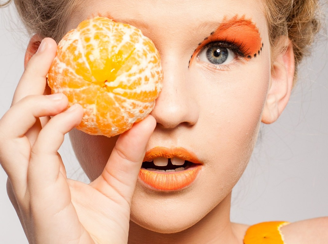 Pretty girl modeling with tangerine