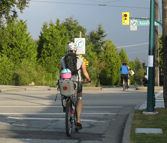 "Another woman who inspires me. This young mother has the extra weight of her toddler on her bike, but she still managed to return my smile and cheerful ""Good morning!"" LOVED the little one's pink and turquoise helmet! And check out those adorable tiny sneakers!"