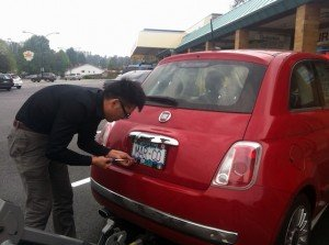 Fiat 500 review - photo of person putting new plates on fiat 500