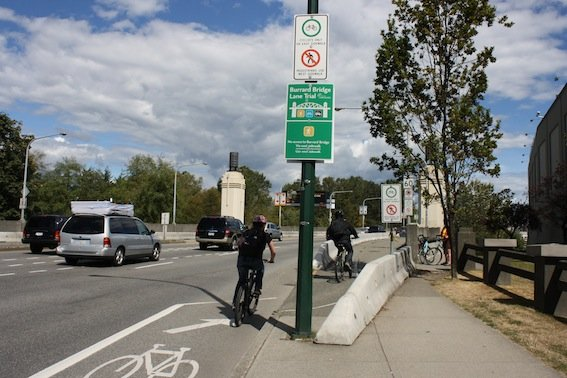 The Amazing Evolution of Vancouver Cycling Infrastructure. Cyclists biking into the safety of the separate bike lane on the Burrard Bridge. The Amazing Evolution of Vancouver Cycling infrastructure
