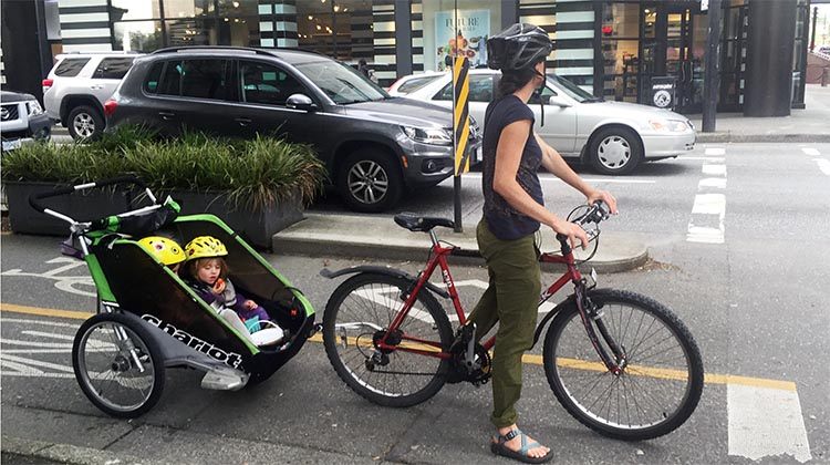 Mom and two kids cycle in relative safety on the Dunsmuir Street separated bike lane in downtown Vancouver. The amazing evolution of Vancouver cycling infrastructure