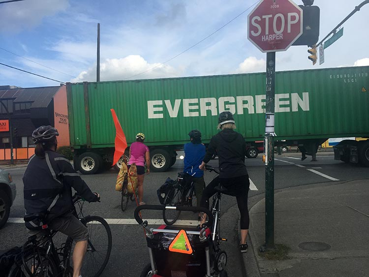 """The Amazing Evolution of Vancouver Cycling Infrastructure. Here's a mom I saw on Adanac Bike Route. They weren't in danger. But anyone who has been at this intersection knows how cars, trucks and bikes jostle for space. And I kind of love the irony in this photo. Mom towing tyke on bike, dwarfed by giant truck - and it's the TRUCK that's labeled """"Evergreen!"""" The amazing evolution of Vancouver cycling infrastructure"""