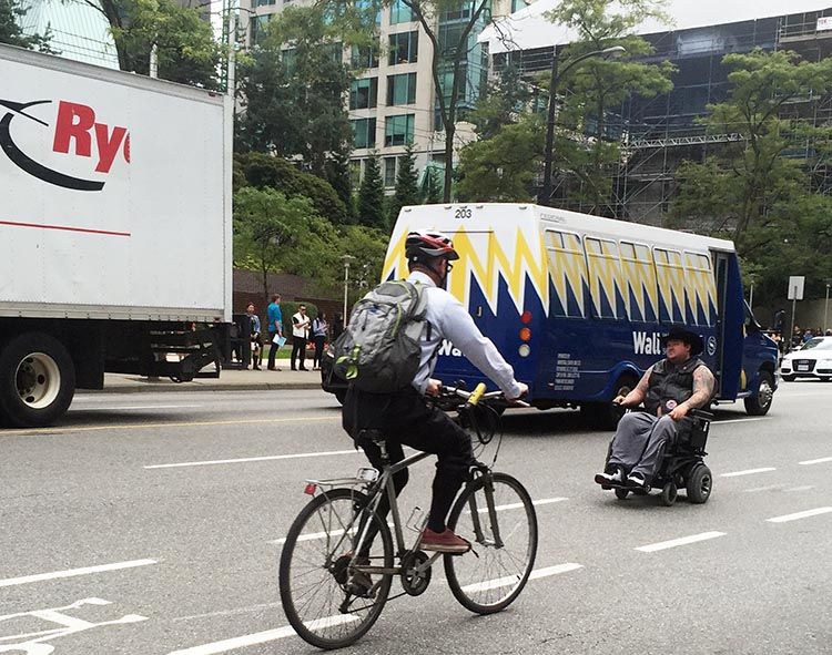 When cyclists (and other vulnerable road users, such as this brave man in a wheelchair) and motorists (including people driving HUGE trucks) are forced to share road space, the vulnerable road users are at real risk of violent injury and death. This photo was taken on Burrard Street in Vancouver, and everyone survived unscathed - that day.