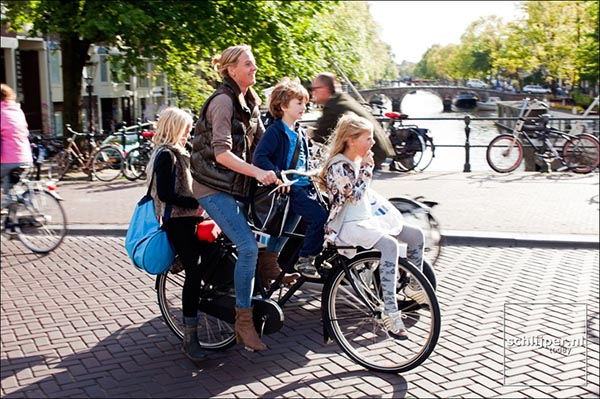 Cycling in Amsterdam - this mom looks amazingly happy and relaxed, even though she is transporting THREE children on a bike! It must help that the nearest cars are so far away that they look like toys