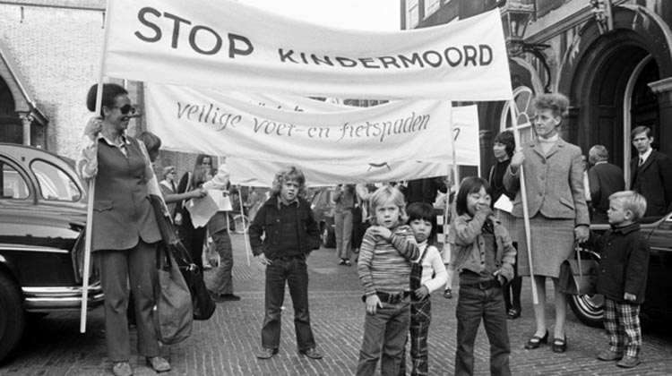 "The Netherlands didn't just magically become safe for cycling, Back in the 1970s, the people DEMANDED safe routes for cycling and walking. These signs say ""Stop Killing Children."" ""Safe walking and biking trails"""