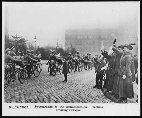 Demobilizing troops transport their kit on heavily laden bikes in Cologne