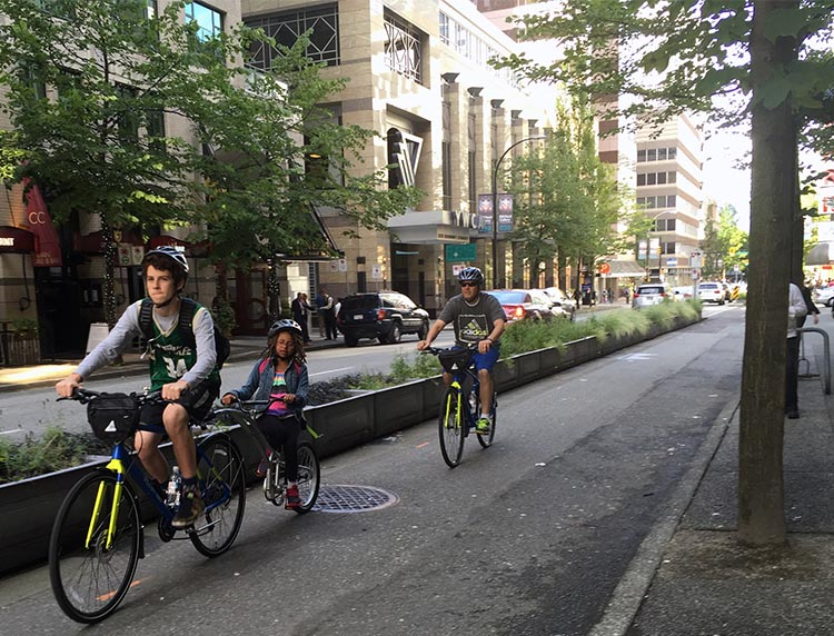 Here is a family cyFamilies can now cycle in downtown Vancouver, thanks to the relative safety provided by separated bike lanes. But shoot - some poor businesses lost a handful of parking spots to make this family of tourists safe - tragic!cling on rendet bikes on Hornby St Separated bike lane.