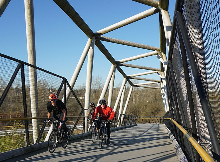 Commuting cyclists on the bridge over Winston Street, an impressive part of the CVG, in Burnaby