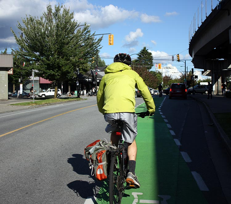 Cyclist approaching Commercial Drive on the Central Valley Greenway