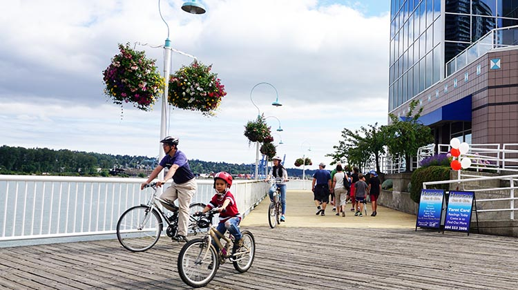 Father and son cycling on the boardwalk on New Westminster Quay. The quay is a great place for kids to practice their cycling skills. New Westminster Cycling