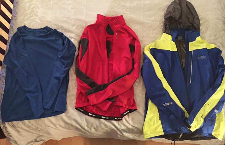 The key to dressing for winter cycling is to wear layers, because cycling warms you up quickly, so you want to be able to peel off layers easily. Above are three layers for the top half of the body: from left, an Under Armor type layer; then my Sugoi Hotshot cycling jersey; and over top a great waterproof cycling jacket