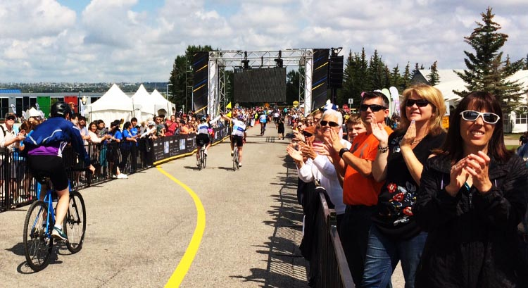 Spectators applaud the efforts of cyclist completing the Ride to Conquer Cancer in Alberta