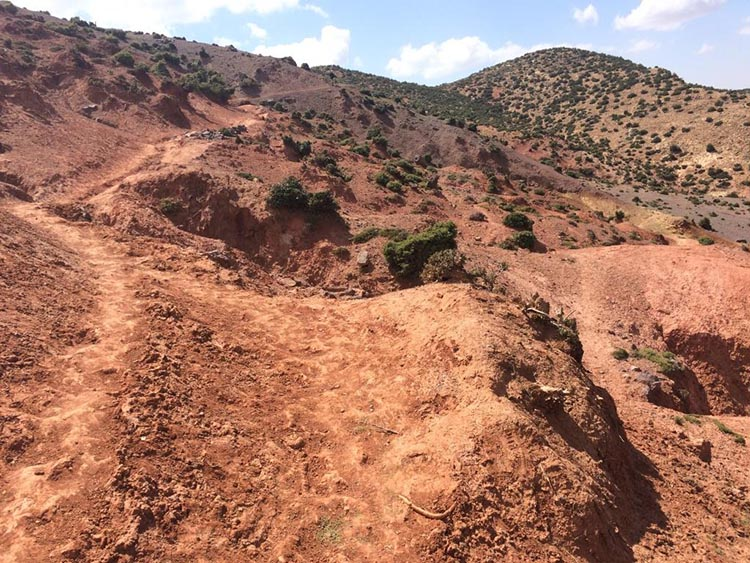 Cycling in the Atlas Mountains in Morocco. The landscape is now a deep red of eroded sandstone