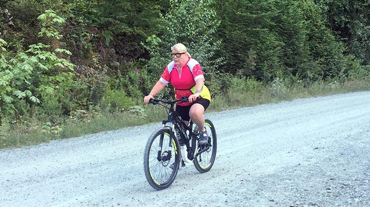 Cycling near Buntzen Lake, British Columbia, Canada. Maggie on her Haibike, zooming along the backroads of Buntzen Lake