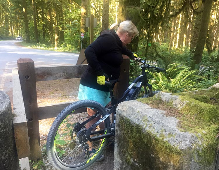 Cycling near Buntzen Lake, British Columbia, Canada. Here's Maggie getting her bike through the turnstile that gives access to the service road off Sunnyside Road.