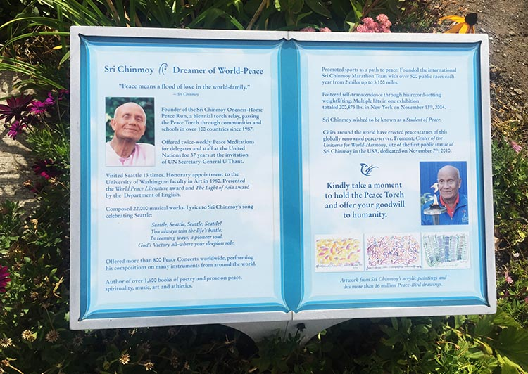 """The plaque next to the statue exhorts you to """"take a moment to hold the peace Torch and offer your goodwill to humanity."""""""