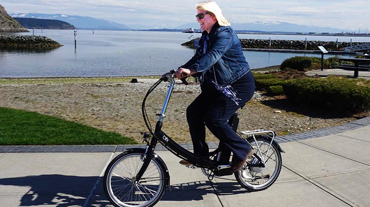 Complete Guide to How to Buy and Sell Bikes on Craigslist. Maggie test riding a folding e-bike in Skagit, Washington