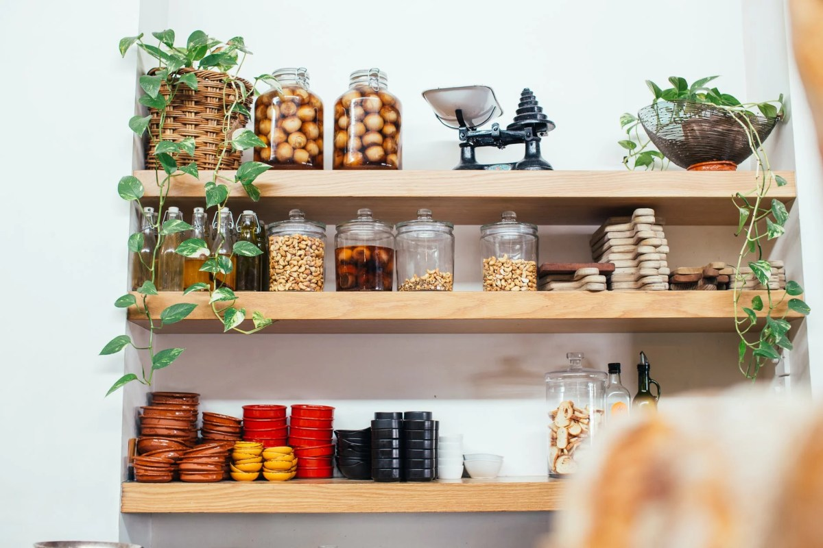 wooden shelves with glass jars filled with various ingredients