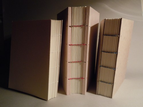 Image of a butterfly stitch binding with folded paper covers, a Coptic binding with wooden boards and red and green thread in the center, and another Coptic binding with uncovered millboard and blue and brown thread on the right.
