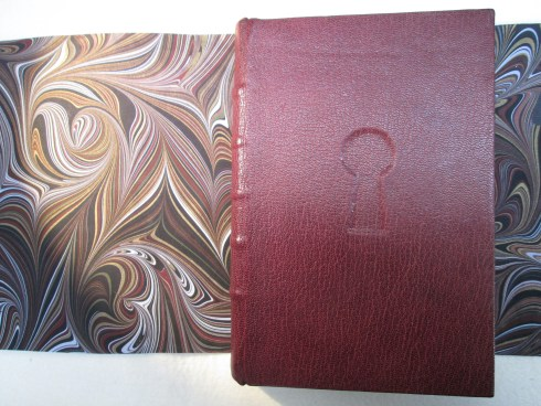 Maroon goat binding with inset keyhole showing marbled endpaper offcut behind