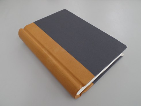 Springback quarter-bound in brown leather with grey cloth and vellum corners