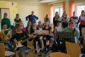 Herr Heims begutachtet die gemeinsame Probe des Chors und des Orchesters.