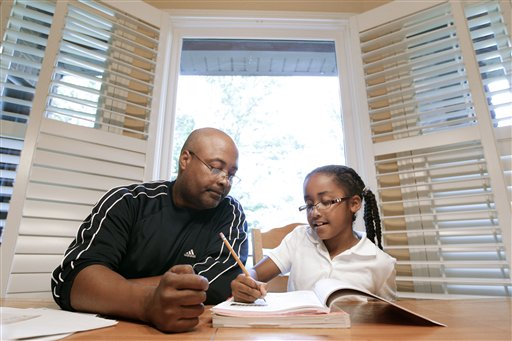Roger Witherspoon helps his daughter, Gabrielle, 9, with her homework in Nashville, Tenn. Tennessee is one of only a few states that has passed laws creating evaluations or contracts that put helping with homework or attending teacher conferences into writing. (AP Photo/Mark Humphrey)