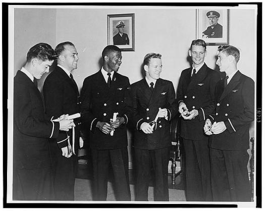 Black male, Ensign Jesse Leroy Brown, posing with five other white male aviation cadets.