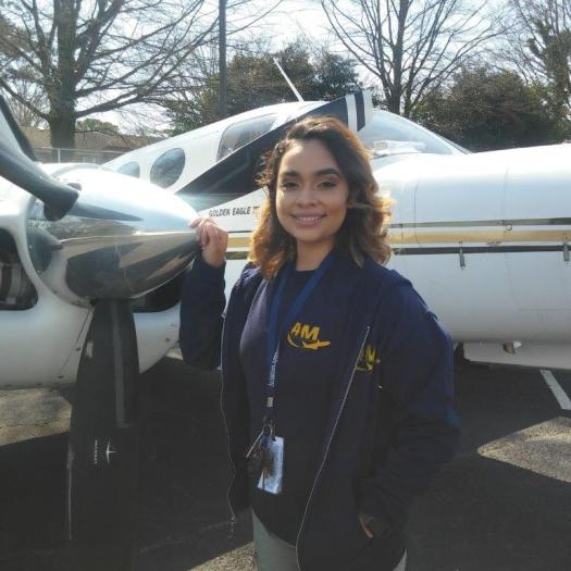 Luz Gonzalez, young woman, pauses next to airplane propeller for Inside MRO interview.