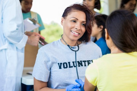 woman wearing grey volunteer shirt smiling while holding stethoscope and talking to person in yellow shirt