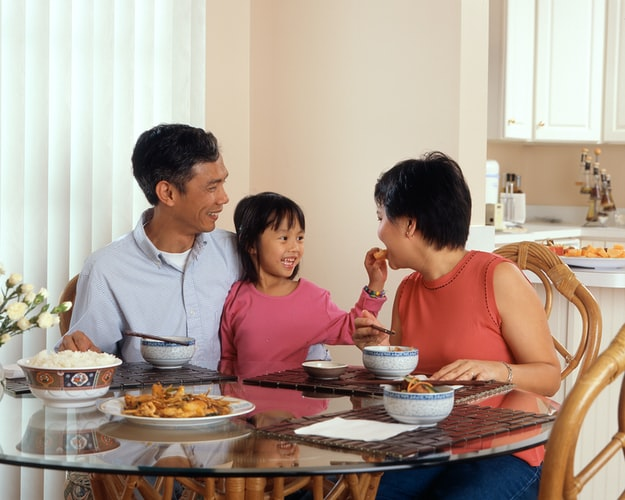 family-with-young-daughter-sitting-around-glass-dining-table-with-dinner-served-in-bowls
