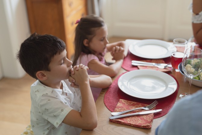 two-children-praying-with-clasped-hands-and-eyes-closed-while-sitting-at-dinner-table