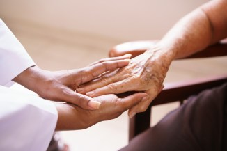 close-up-of-doctor's-hand-holding-hand-of-elderly-patient-while-both-sit-face-to-face