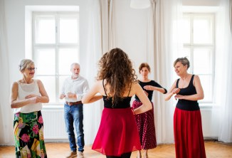 dance-therapist-demonstrating-movement-in-front-of-four-seniors