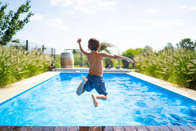 snapshot-of-young-boy-wearing-blue-swim-trunks-jumping-into-pool-on-hot-summer-day