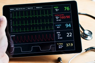 Doctor holding a digital tablet with a live recorded ecg on it. On the desk in the background is a stethoscope.