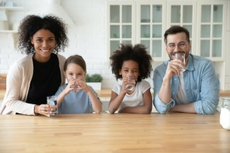 family-with-two-girls-sitting-at-table-drinking-water-from-glasses