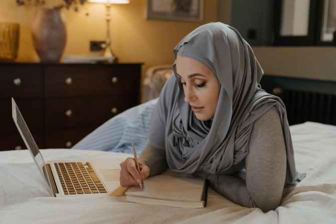 woman in gray hijab using macbook air