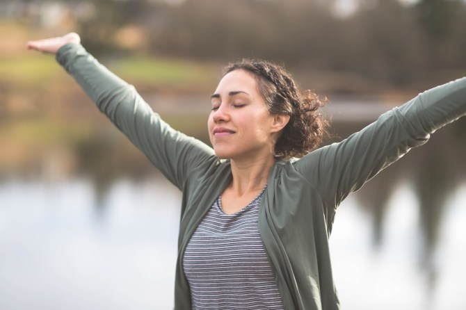 young-woman-wearing-grey-cardigan-raising-arms-while-smiling-outdoors-by-pond
