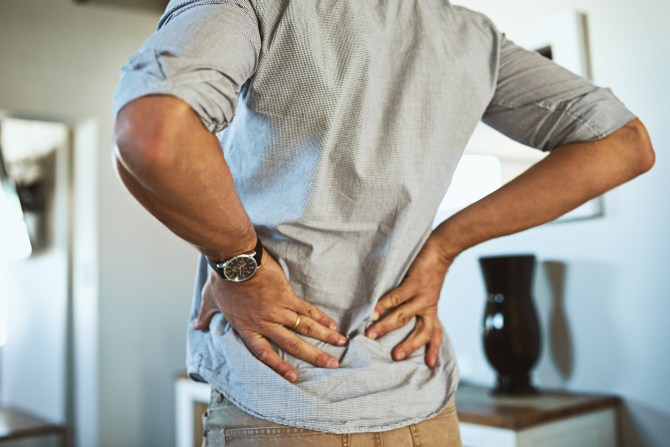 cropped-photo-of-man-holding-lower-back-with-both-hands-in-home
