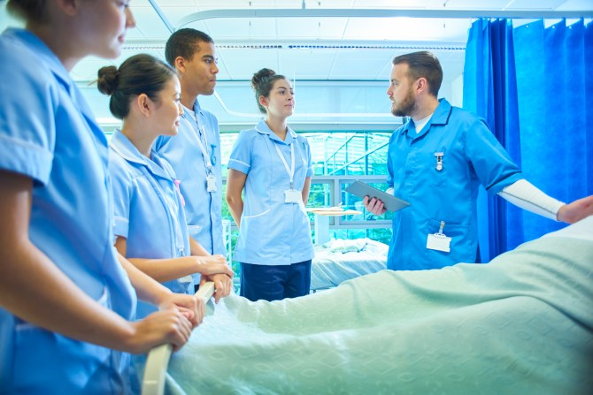 A  senior male staff nurse demonstrates the medical mannequin to a group of medical student nurses . They are all standing around the hospital bed listening to him .