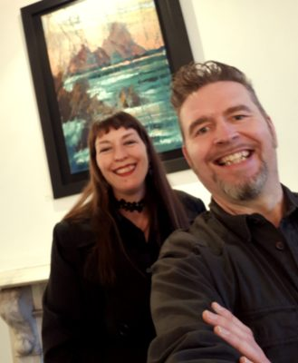 """Rod amuses his muse Anja Coyne at the Seeing Red launch with """"Skellig Blush"""" 70x100cm oil on canvas in the background."""
