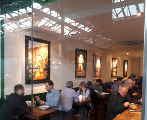 Photo shows Diners at Tossed Noodles enjoy lunch surrounded by Rod Coyne's art.