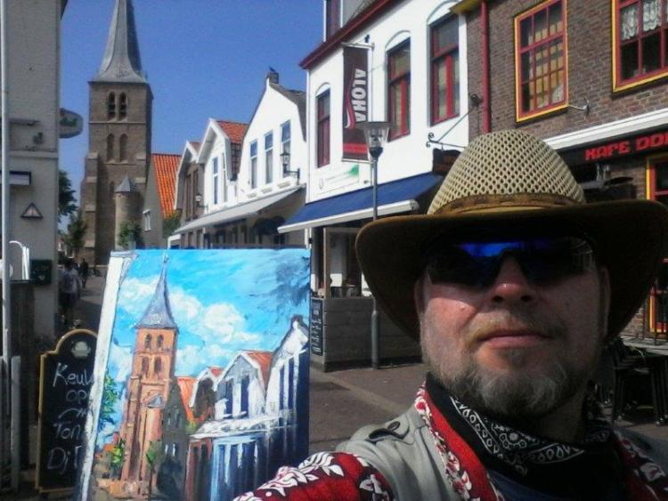 Photo of rod coyne's last day painting in domburg. mondriaan's church, and rod's piainting of same, visible over the artists shoulder