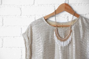 silver dress and necklace on wooden hanger, hanging against a brick wall that has been painted white