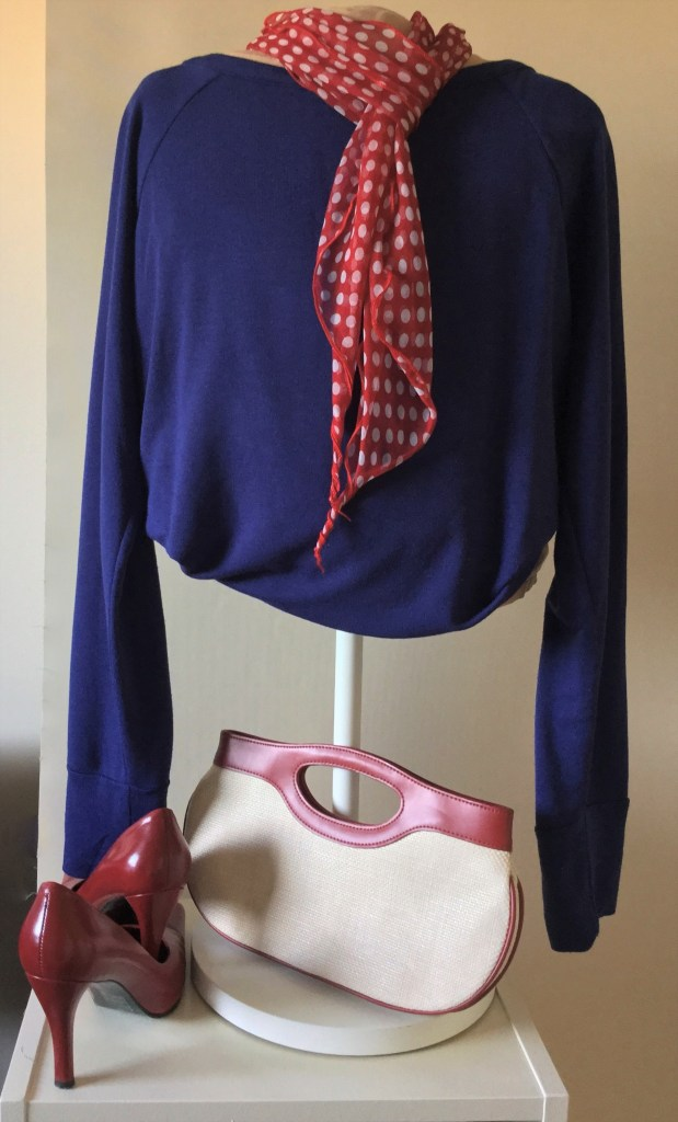 blue top on mannequin with red shoes and accessories