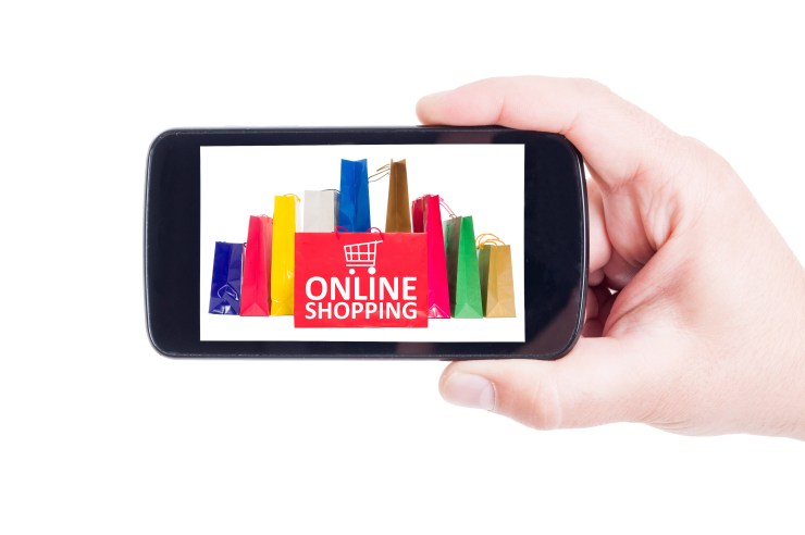 "personal shopping:  someones hand holding a mobile phone showing an image of shopping bags and the text ""online shopping"""