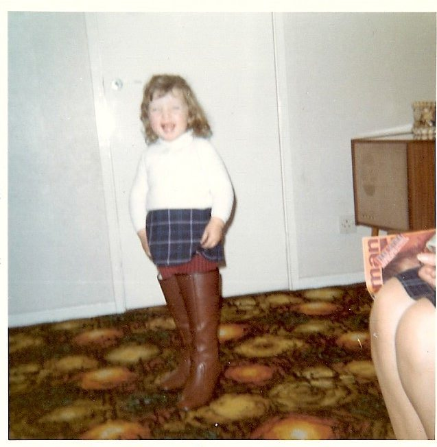 A young girl about 3 or 4 years old smiling happily. Playing dress up in a pair of ladies brown leather knee high boots with her navy tartan mini kilt and cream jumper. Standing on a swirly 1970s livingroom carpet