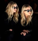 FEBRUARY 15: Ashley and Mary-Kate Olsen watch models display designs from the J. Mendel Fall 2012 collection during Fashion Week in New York. (Associated Press)