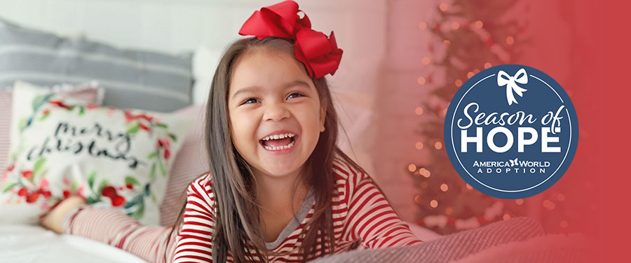 A smiling young girl in Christmas colors smiling at the camera